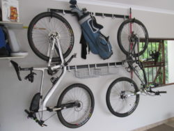 Our hook and rail systems is popular in garages especially to hang bikes against garage walls. In the image some other hooks are added to the rail to hang helmets and more