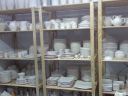 Image of crockery packed on shelves in store front end.
