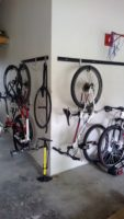 These 2 hook and rail systems are hanged on the corner in a garage to hang bikes and bicycle accessories