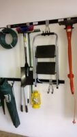 Hook and Rail system used in this garage to hang a variety of gardeining utensils including weateater, hosepipes, spades and more. Below this is another hook and rail system used for smaller items..