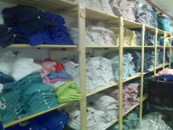 Image of shelves used in store back end. The shelving in this imag stores clothing, our shelves are perfect for this as our shelves allows airflow preventing mouldy and damp smells.