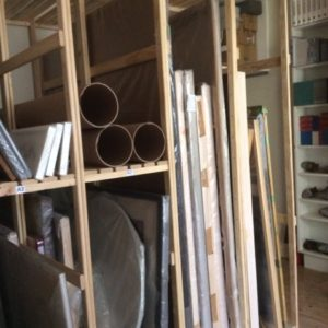 Picture of shelves with canvases big and small on a variety of different sized shelfs