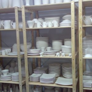 Lots of crockery items on shelves in hotel kitchen