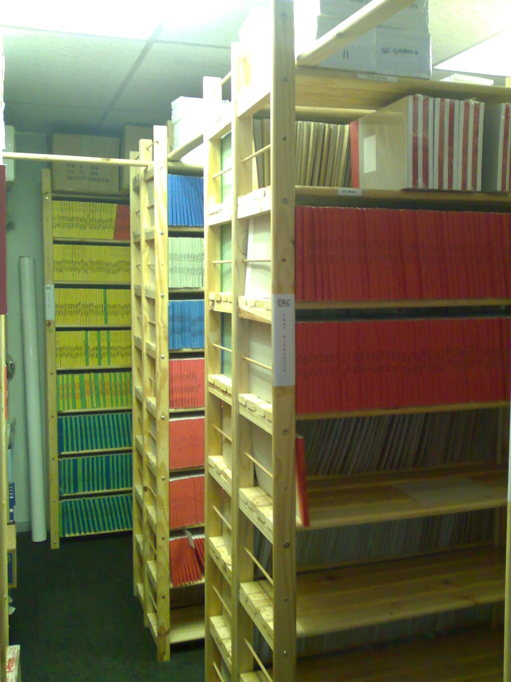 Image of files on and archives in storeroom shelving unit. This filing storeroom shelves has been customised to include as much as possible on one shelf without loosing capacity.