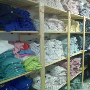 Shelves used in the back storeroom of a shop with clothing on the shelves